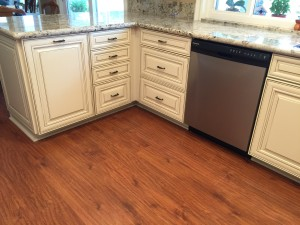 flooring contractor installs wood floor to contrast with shaker cabinets